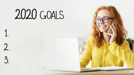 Target Business development to success in 2020. Cheerful girl talking on phone and working on laptop, goals checklist with empty space