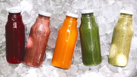 Healthy breakfast. Five day ration of different fresh detox drinks in glass bottle on ice background, panorama Stockfoto
