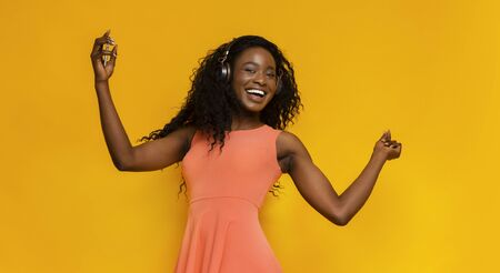 Carefree african american girl enjoying rhythmic sound, dancing and listening to music on yellow background, panorama