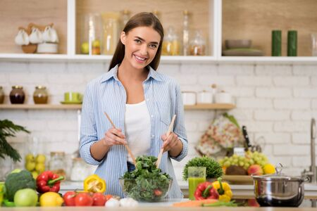 Happy woman mixing fresh vegetable salad in kitchen, cooking dinner and looking at camera