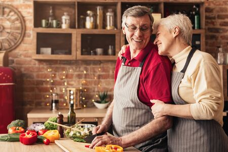 Lovely seniors embracing at kitchen, caring man cutting vegetables for salad, empty space