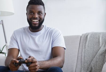 Millennial african american guy playing video games at home, holding joystick in hands, free space 免版税图像