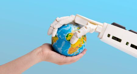Future technology and artificial intelligence concept. Human and robot hands holding earth globe, blue background Stok Fotoğraf