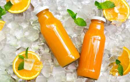 Blended vegetables. Carrot smoothie in glass bottle with fresh oranges on ice cold background, panorama Reklamní fotografie