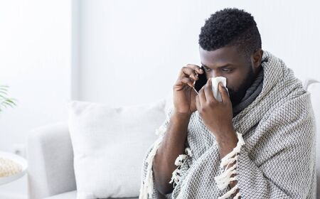 Call for help. Sick black guy calling an ambulance, caught flu, empty space Stock Photo