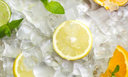 Summer background with lemon slice and oranges on ice cubes background, panorama Фото со стока