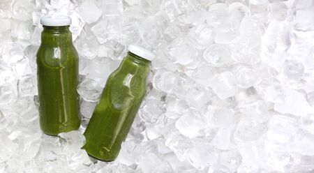 Healthy lifestyle. Vegetable detox blended drink in glass bottle on ice cubes, panorama, free space