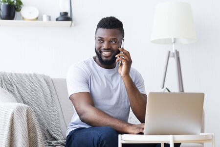 Pleasure talk. Cheerful african-american man talking on phone and working on laptop Foto de archivo