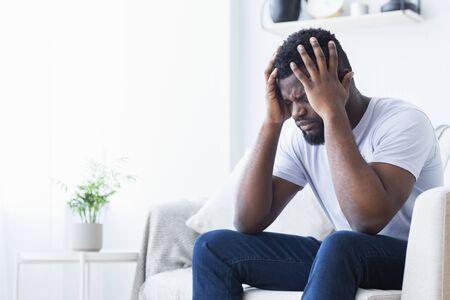 Agota la migraña. Joven afroamericano que sufre de dolor de cabeza en casa, espacio de copia