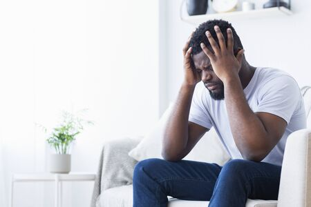 Erschöpfende Migräne. Junger afroamerikanischer Mann, der zu Hause unter Kopfschmerzen leidet, Kopienraum