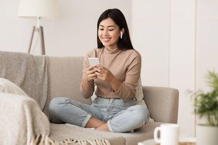 Chica estudiante relajándose en el sofá en casa, escuchando música y charlando por teléfono Foto de archivo