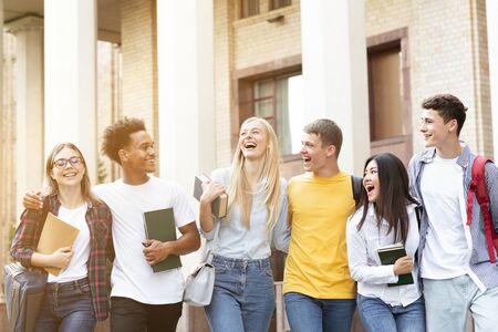 Heureux étudiants marchant ensemble sur le campus, faisant une pause à l'université