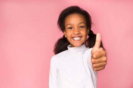 I like it. Happy girl showing thumb up on pink background