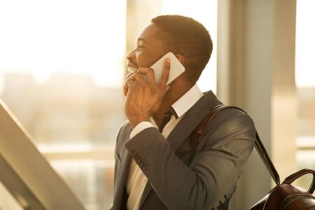 Afro Financier Talking on Phone in Airport Terminal, Waiting for Plane