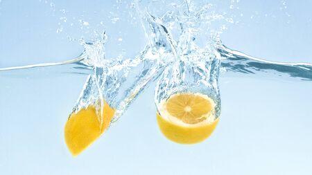 Citrus detox. Cut fresh lemons in clear water with splash, blue background Banco de Imagens