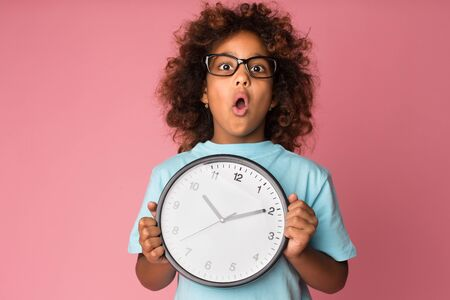 Shocked schoolgirl holding big clock, looking at camera over pink background