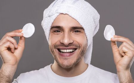 Morning procedures. Young man with cleaning face with cotton pads with towel on his head, smiling at camera