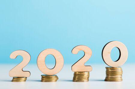 Concepto de ahorro de dinero. Grandes números de madera 2020 en monedas que muestran crecimiento financiero, espacio de copia