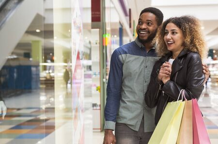 Happy african couple fell in love with beautiful wedding dress in shopping center, free space
