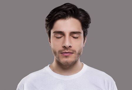 Portrait of handsome millennial man with closed eyes, grey studio background