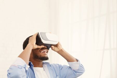 Happy young african-american man with virtual reality headset or 3d glasses playing video game at home, copy space