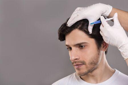 Man met haaruitvalprobleem krijgt injectie in hoofd, grijze achtergrond, lege ruimte Stockfoto