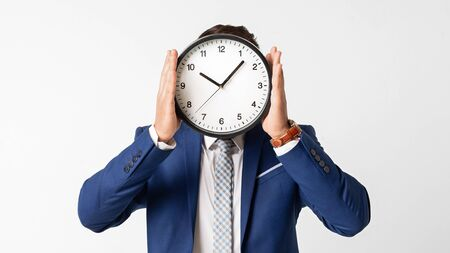 Time management concept. Businessman covering his face with clock on white studio background. Panorama, empty space