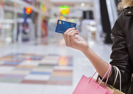 Easy Pay. African american woman with credit card making purchases in shopping center, copy space