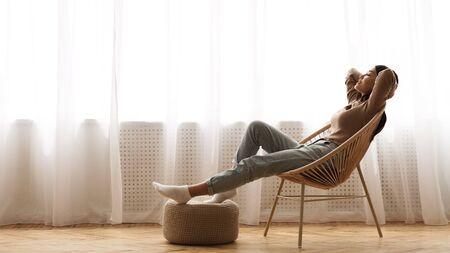 Perfekter Morgen. Mädchen sitzt im Sessel am Fenster und genießt die Freizeit