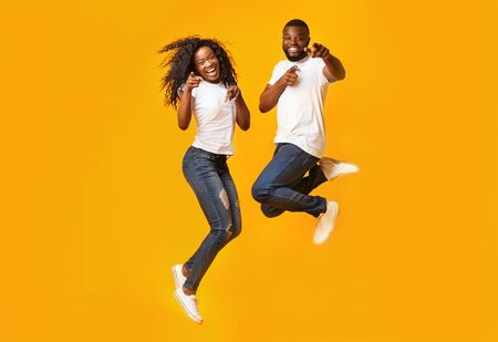 Carefree Black Millennial Man And Woman Are Jumping In The Air, yelllow background