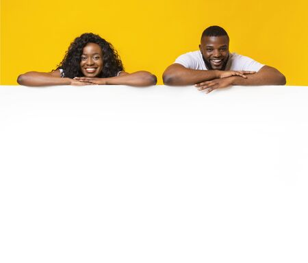 Free Space For Advertising. Afro couple is leaning on empty white board, yellow background Imagens