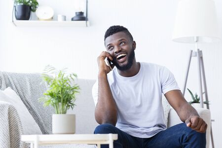 Talkative african guy talking on phone with friends, sitting on couch at home, empty space Stock Photo
