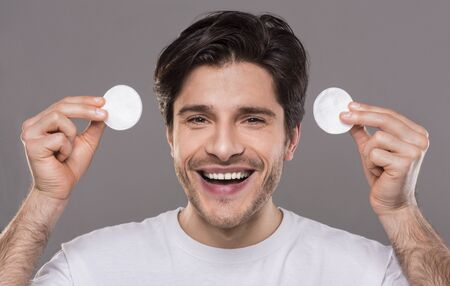 Clear skin and wellness. Cheerful man holding cotton pads for face cleaning