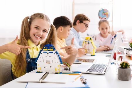 Stem education. Girl showing her robot. Proud student of her project Stock Photo