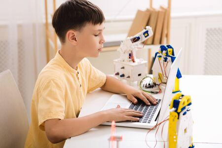 Boy creating robotics project on laptop, typing plan of innovation robot model Stock fotó