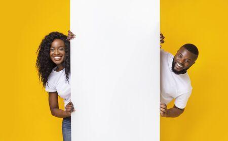 Black Girl And Guy Holding White Advertising Board, yellow studio background, panorama
