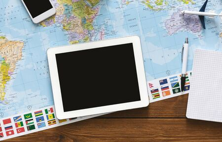 Tablet with blank screen laying on world map, panorama