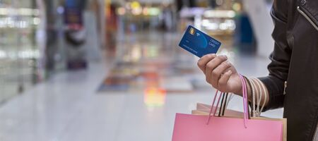 Pay pass. African woman with credit card doing shopping in big mall, panorama, free space