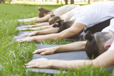Group of people lying in a row with face down on yoga mats making Child pose, side view Banco de Imagens