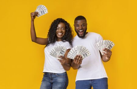 Happy Black Couple Holding Dollars, yellow studio background