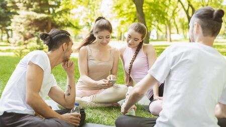Portrait of cheerful young friends looking at smart phone while sitting in park after practicing yoga.