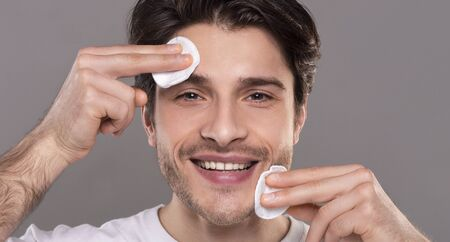 Male skin care. Positive guy cleansing face with cotton pads, panorama
