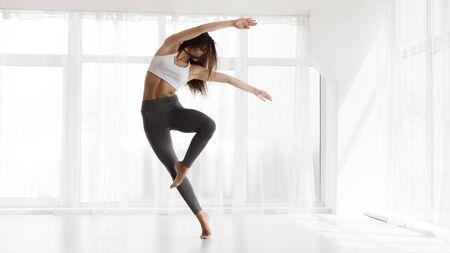 Hübsches Mädchen, das Contemp und Ballett im modernen Tanzstudio tanzt. Panorama, leerer Platz für Text