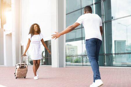 Happy black man meeting his girlfriend with opened arms at airport