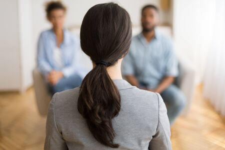 Couples Therapy Session. Counselor Listening To Afro Husband And Wife Sharing Problems In Office. Back View, Selective Focus, Copy Space Foto de archivo