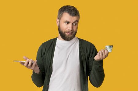 Why I Need Credit Card If I Have Cellphone? Caucasian man doubtfully looking at plastic card, yellow studio background Banque d'images