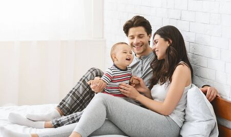 Cheerful millennial man and woman playing with baby son, sitting together on bed, free space