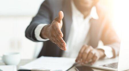 Schwarzer Geschäftsmann, der vor der Kamera Hand zum Händeschütteln gibt und Partnerschaft vorschlägt. Panorama