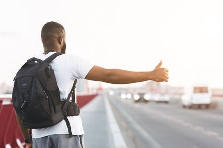 Young Black Guy Is Hitchhiking On The Bridge Road, carrying backpack, rear view Reklamní fotografie