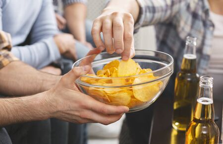 Close up of man holding bowl with chips sharing with friends at home party